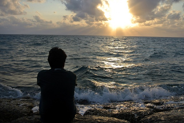 A person watching a sunset on the beach.