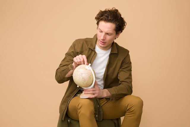 A man looking at a globe trying to cope with moving to another country